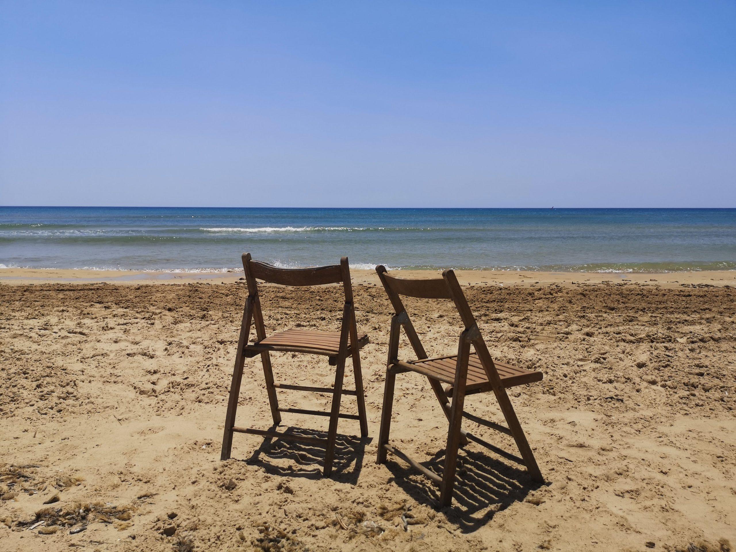 spiaggia con due sedie di legno pieghevoli che guardano il mare