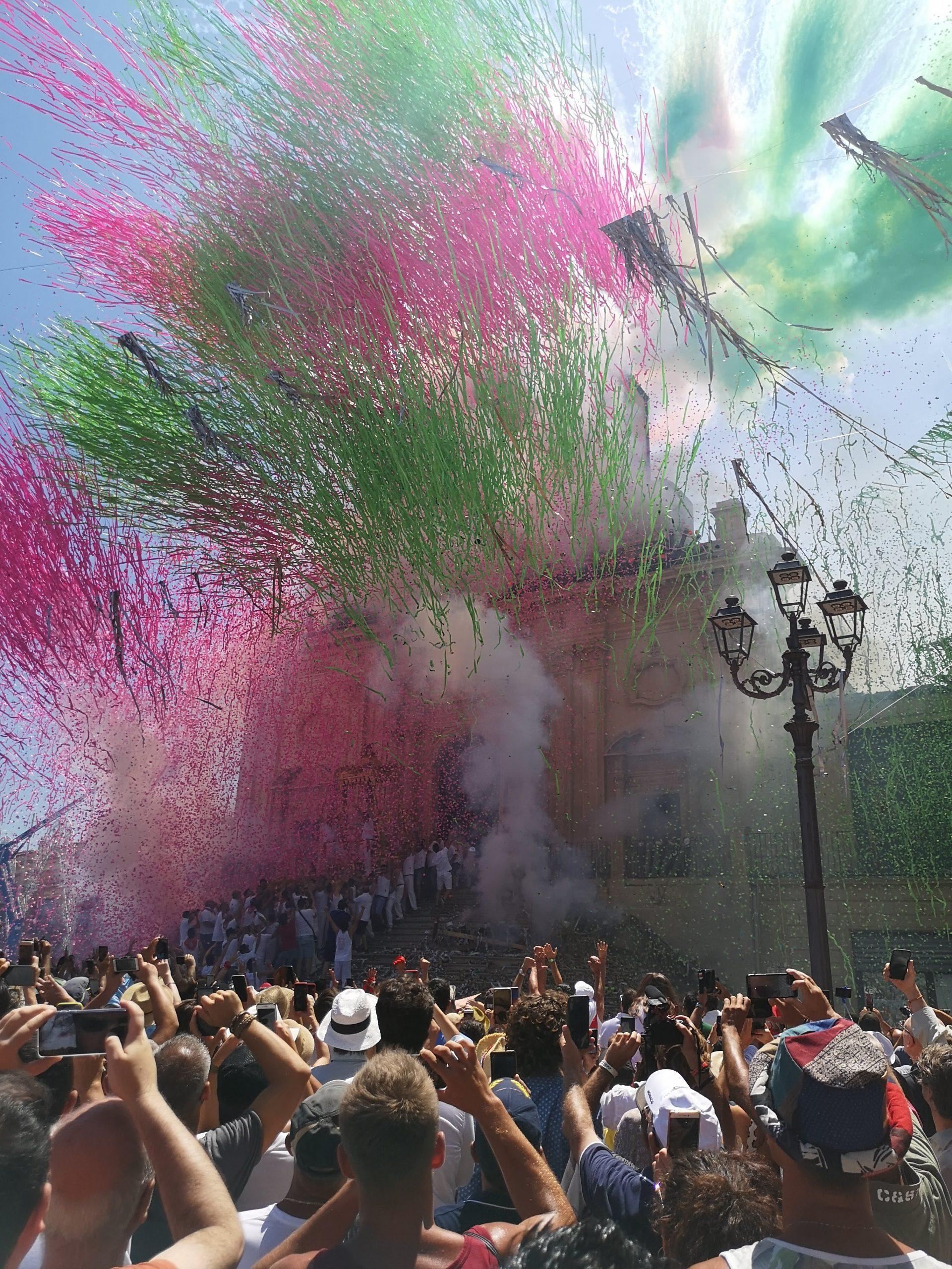 strisce di carta colorata verde e rosa sparate davanti la facciata della chiesa