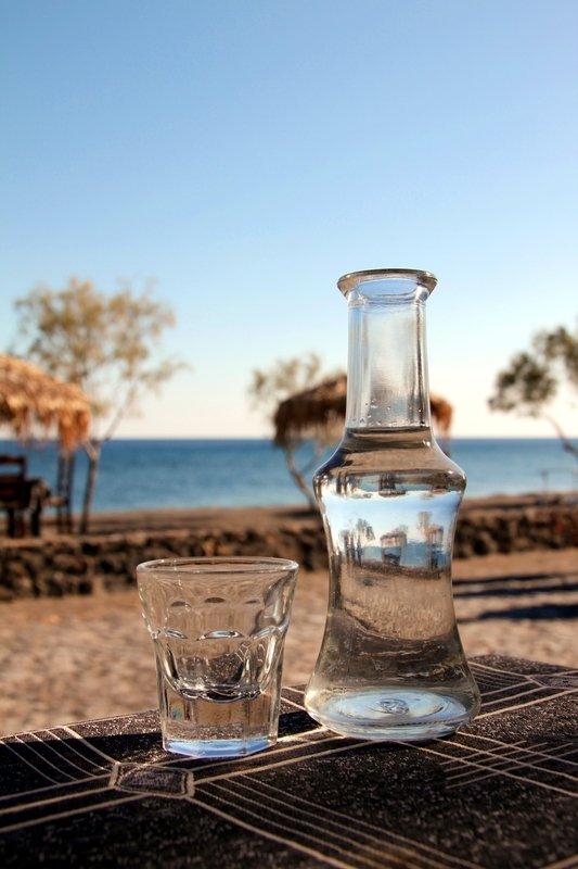 bottiglitta tsipouro grecia su tavolo con sfondo del mare